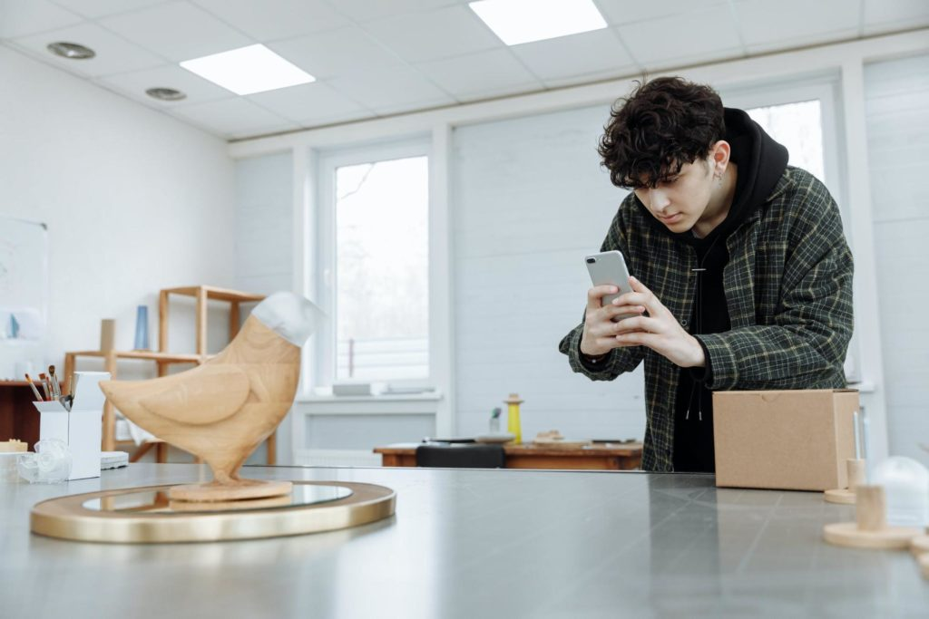 Young man wearing plaid jacket in an art studio documenting a bird sculpture with his phone.